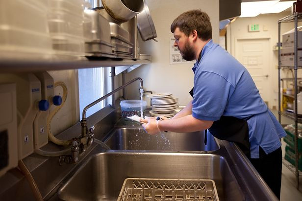 Image of Matt Cloughley, wearing a blue polo shirt and black apron, washing dishes at the sink in the BHMA commercial kitchen.