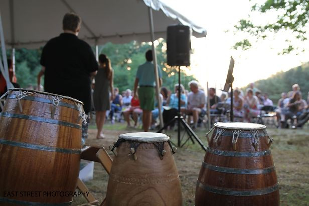 Image of three African drums in the foreground, with music equipment, a small audience, and a setting sun visible in the background.