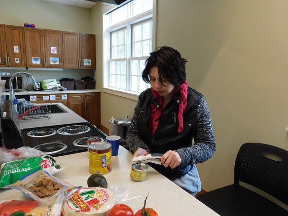 Picture of Heather Silva, wearing a black leather jacket and pink scarf, using a can opener at her cooking station in the student kitchen.