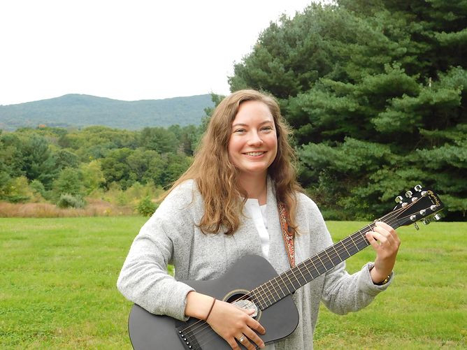 Image of Allie, wearing a white blouse under a light gray sweater, playing a small black guitar in BHMA's backyard under an overcast sky.