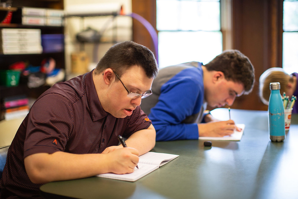 Image of Ben Krifka (foreground) and Connor Thompson (background) writing in open notebooks; both have a look of concentration on their faces.