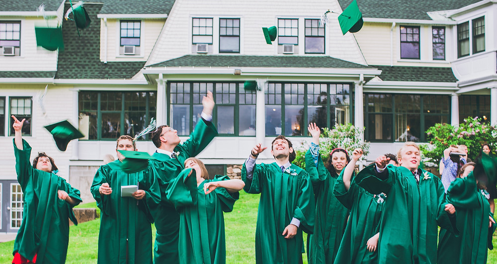 Image of nine graduates dressed in green robes tossing their caps in the air; the back of BHMA's main building is visible in the background.
