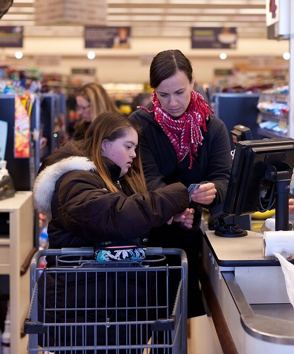 Image of Danielle Kelly, wearing a pink scarf and black jacket, assisting student Emma as she starts to pay for her purchase at the grocery store.