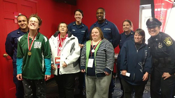 Image of Mary Westgate, wearing her green BHMA Kingpins polo shirt, poses with her gold medal around her neck; she is pictured with two other medal winners and six other volunteers.