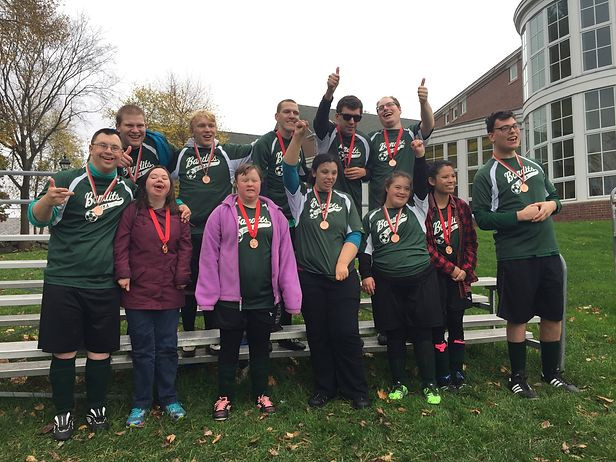 Group photo of twelve members of the Bandits soccer team posing on the bleachers with their medals.