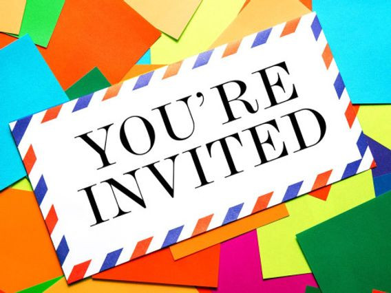 """Image of a white letter with blue and red lines around the border with the text """"YOU'RE INVITED"""" printed in black; it is angled diagonally and sits on top of several colorful squares of paper."""