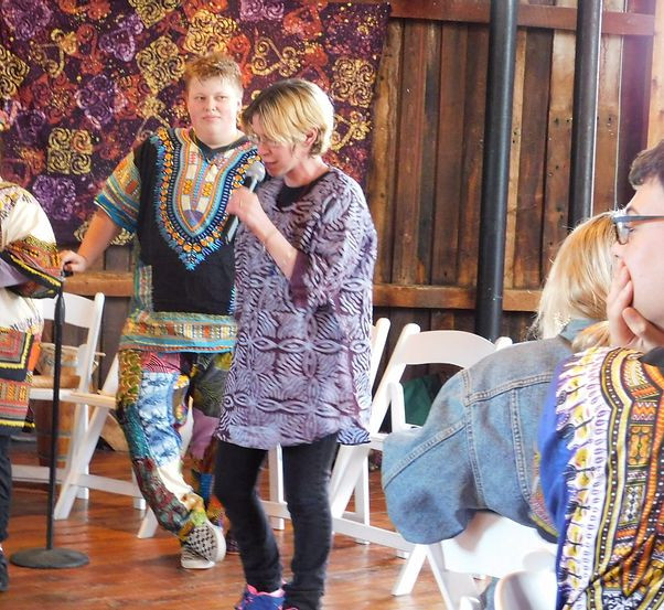 Image of Emily Webster, wearing a purple dashiki, speaking at the Red Barn at Hampshire College.