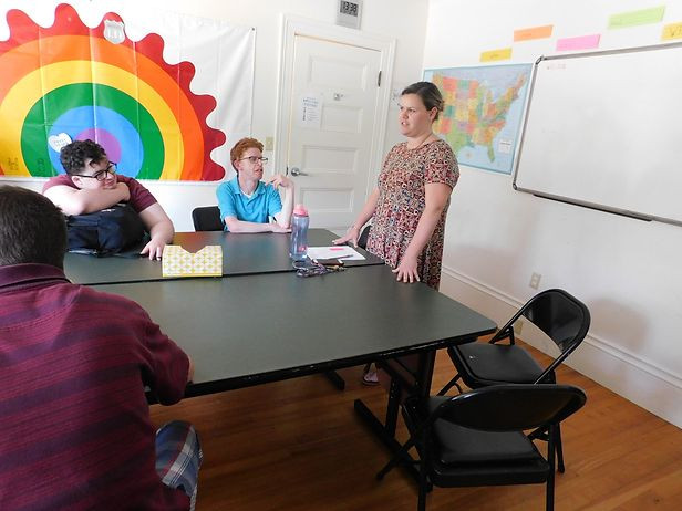 Image of Maddie Mercier standing before a table as she teaches a class in the Life Skills classroom.