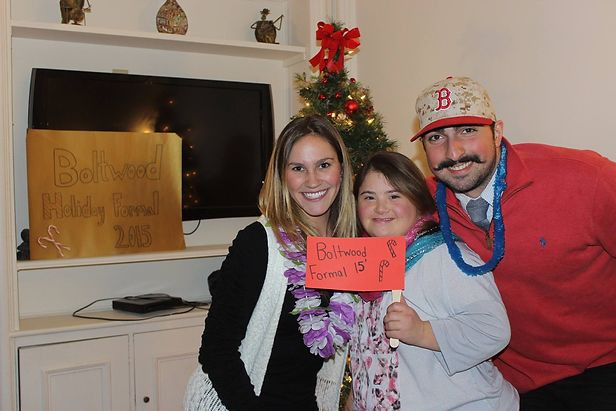 Emma Pignone posing with two UMass students at the holiday party.