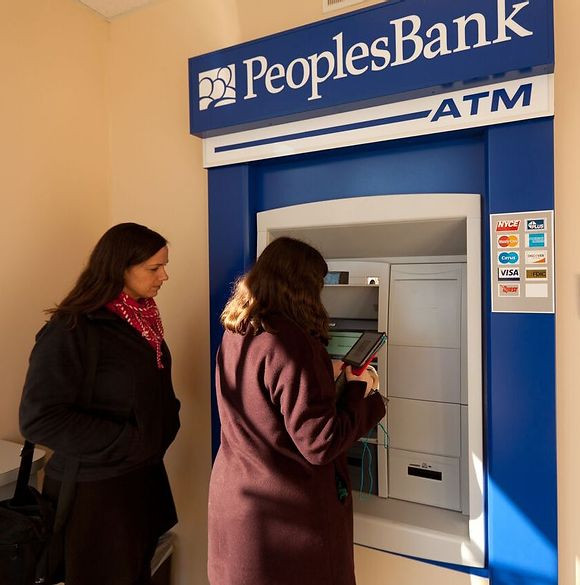 Danielle Kelly, wearing a pink scarf and black jacket, looks on as student Carly uses the PeoplesBank ATM.