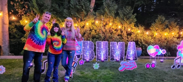 Image of Joe, Paige, and Karen Phillips dressed in colorful tie dye posing outside in front of BHMA lawn decorations.