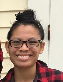 Picture of Ana Li Harper, wearing glasses and a black and red plaid shirt smiling in front of a building with yellow siding.