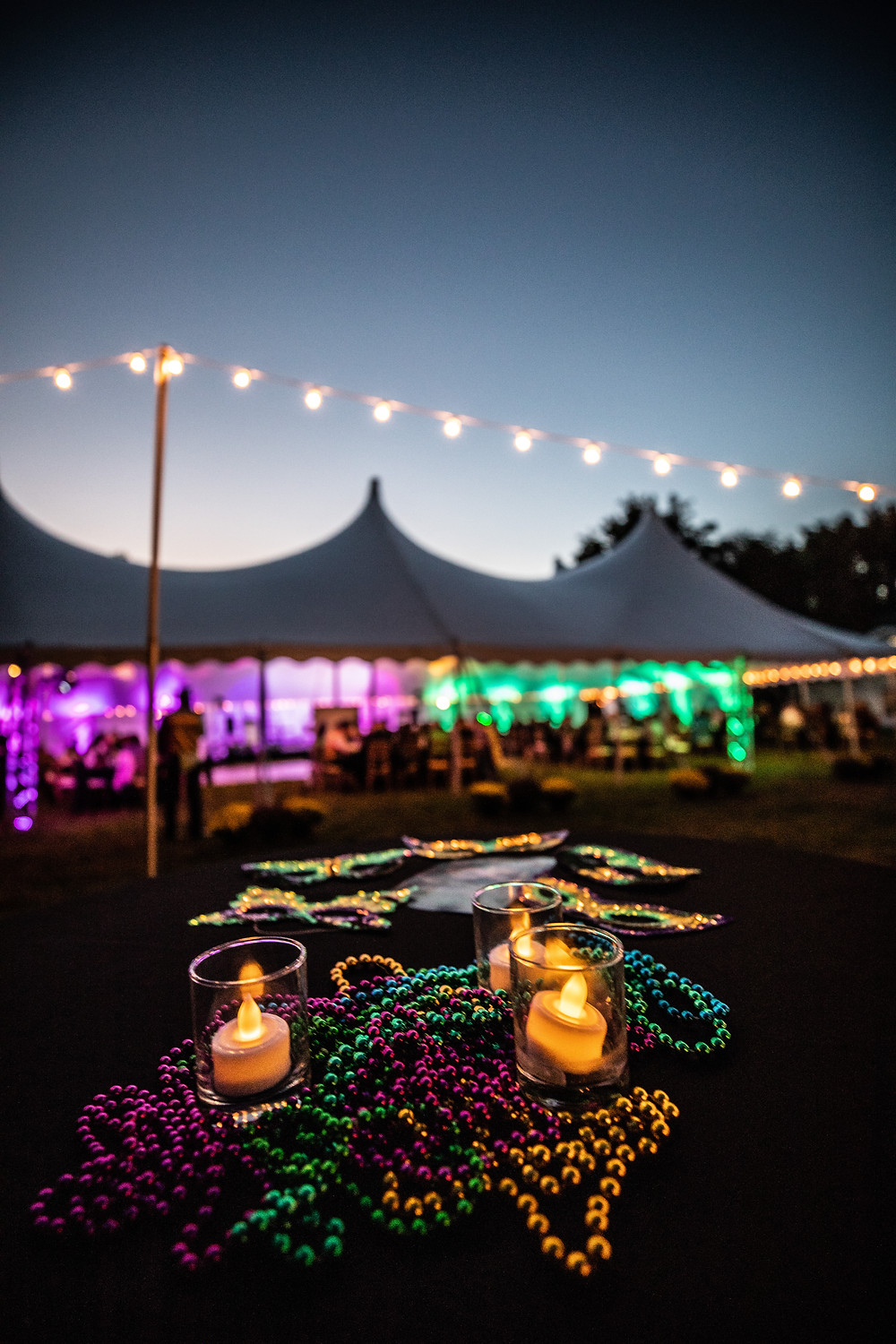 Photo of beaded necklaces, lit electric candles, and Mardi Gras masks strewn on a table; in the background a string of lights and the illuminated party tent are visible beneath the fading blue sky.