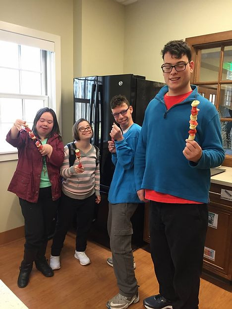 Image of Jen Barrett, Ilyse Ross, Andrew Gaudioso, and Michael Gumbardo posing in the student kitchen with their kebabs.