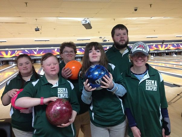 Image of six members of the BHMA Kingpins team posing together in their uniforms at the bowling alley; four members hold bowling balls in their hands.