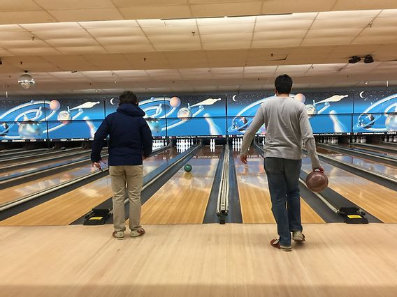 Image of two students, with their backs facing the camera, bowling at Spare Time Northampton.