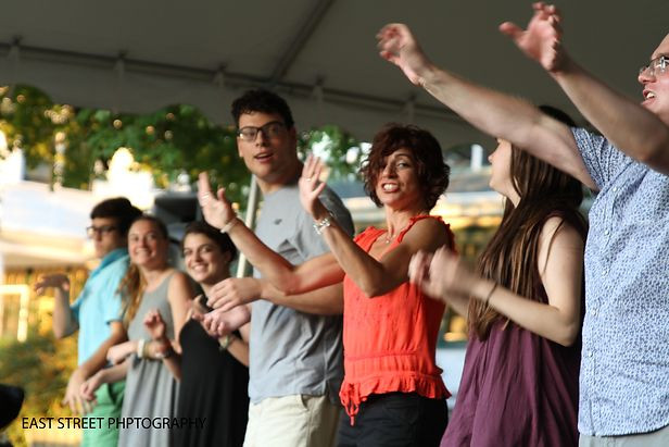 Photo of seven Summer Program participants and staff members dancing under the tent at the final concert of the 2016 Summer Program.