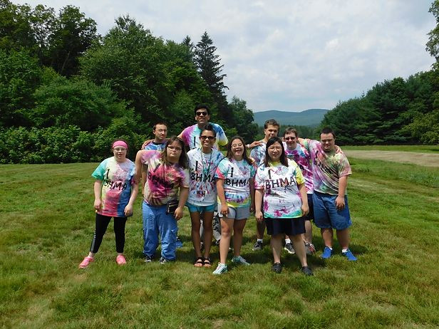 Image of ten students wearing tie-dye shirts posing together in BHMA's backyard; green grass, trees, and partly cloudy sky are visible in the background.