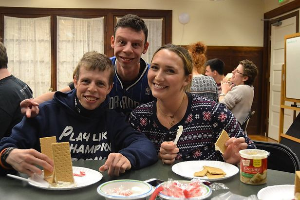 Image of Tim Connor, Andrew Gaudioso, and a UMass student posing together as they make gingerbread houses in the BHMA kitchen.