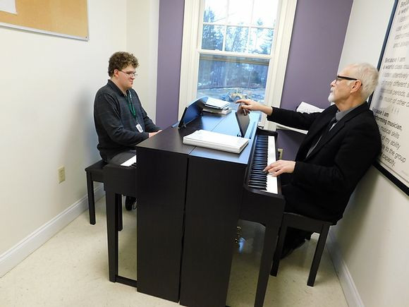 Image of Mark Palardy, seated at the left piano, and Tom Slowick, seated at the right piano, in the middle of a piano lesson in the BHMA purple studio.