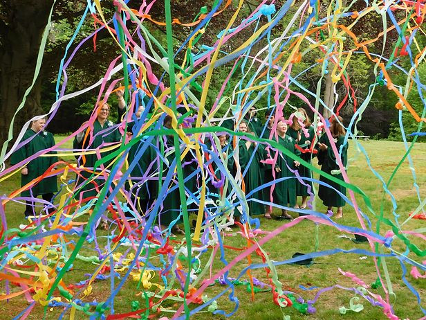 Image of rainbow streamers launched as the class of 2017 toss their caps.