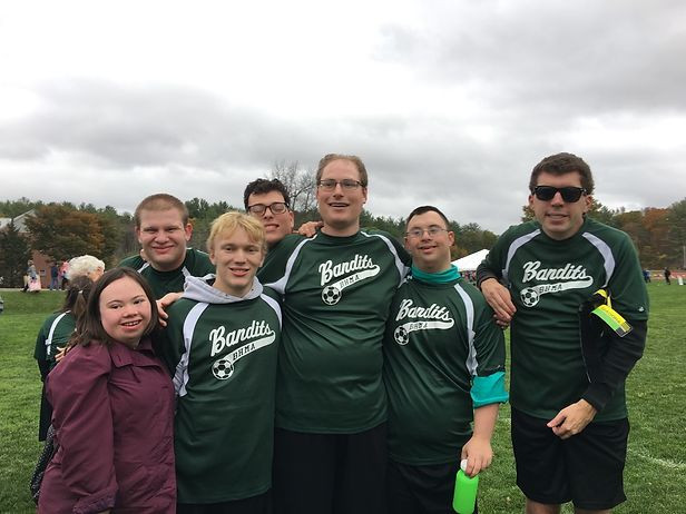 Image of seven Bandits team members posing together between games; an overcast sky is visible in the background.