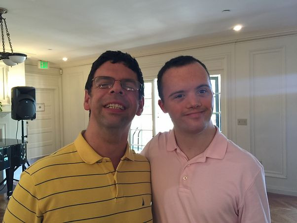 Image of John Libera, left, wearing a yellow and blue-striped polo shirt, posing next to Graham Campbell, right, wearing a light pink polo shirt; they are standing in the Great Room.