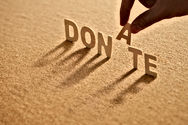 """Donate Image, Hand placing the letter """"A"""" into the word """"DONATE"""" on sand -  Image links to become a member"""