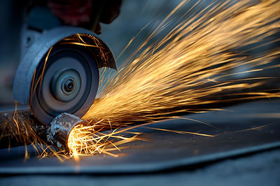 Worker cutting metal with grinder. Spark