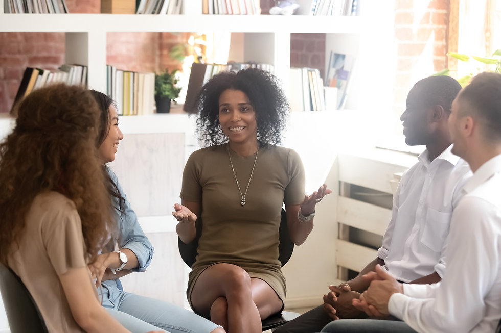 Smiling African American psychologist counselling, speaking with diverse people sitting in