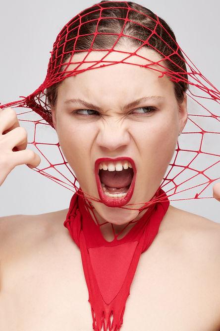 Model zerreisst rote Netzstrumpfhose vorm Gesicht