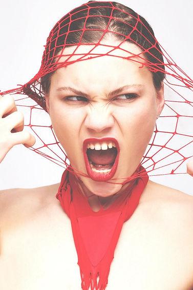 Frau reisst sich rote Netzstrumpfhose vom Gesicht