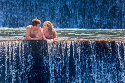 Happy Couple Swimming In Natural Spring Waterfall Pool