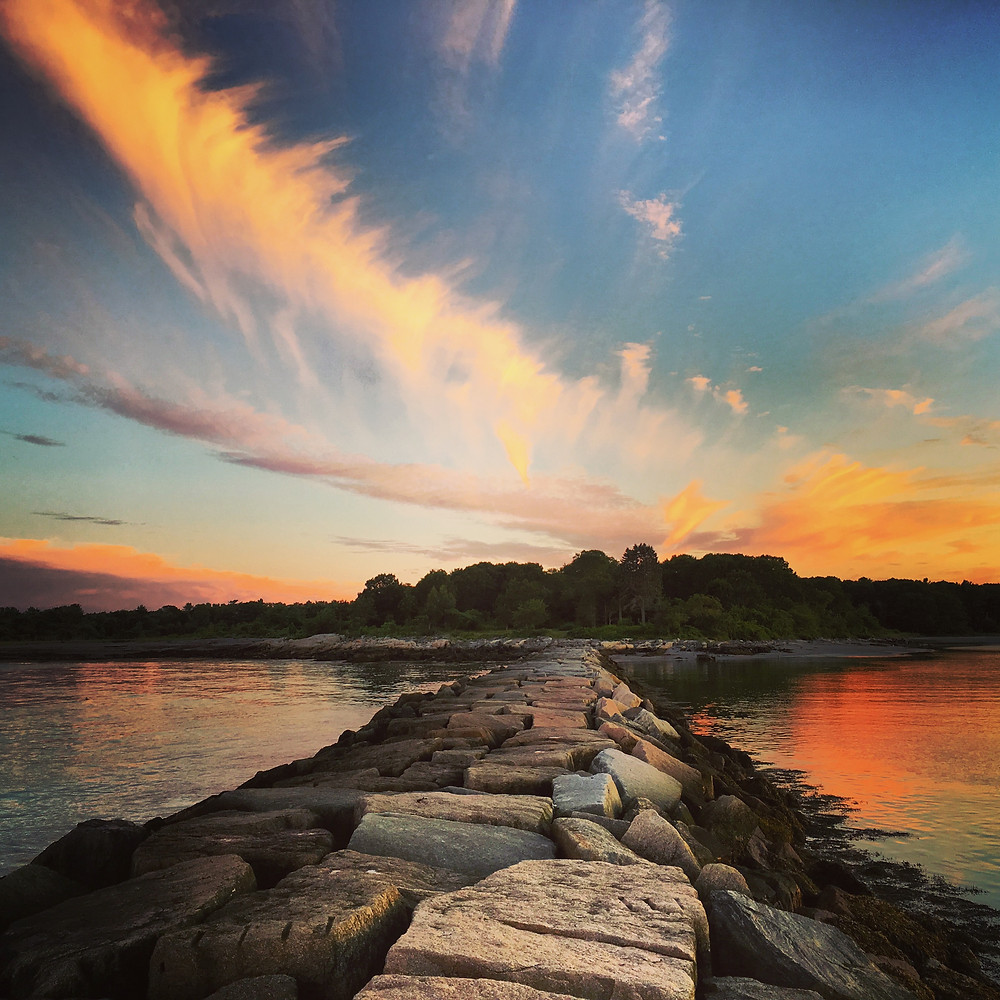 brilliant blues, oranges, yellows, purples, and whites streak the clouds over a long jetty at Odiorne Point State Park in Rye, New Hampshire