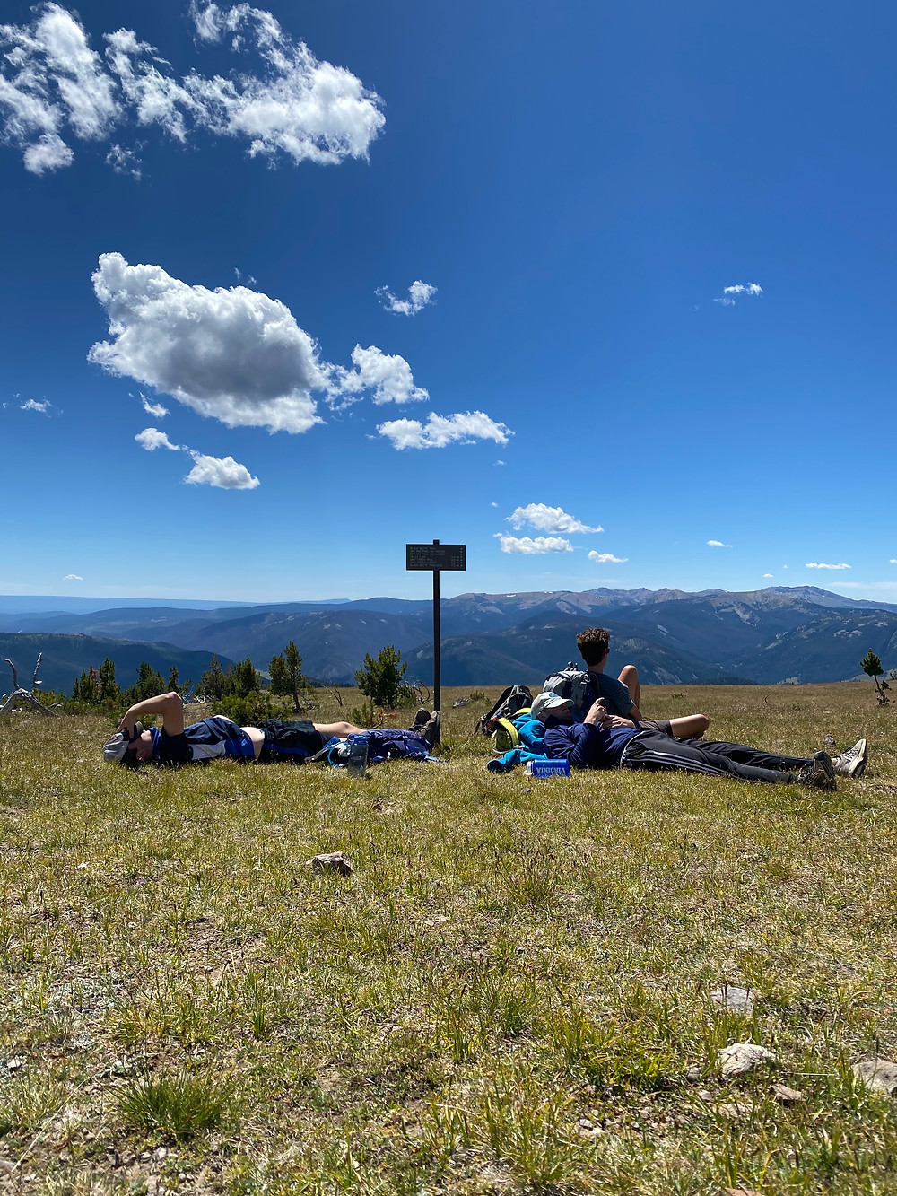 Brilliant blue skies give Sky Rim its name. Several hikers look exhausted lying on the grass at the top after reaching the lofty peak in Yellowstone National Park