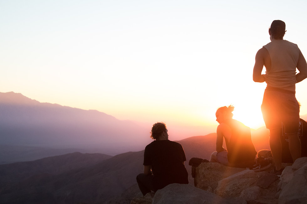 Hikers at a mountain summit looking at the sunset
