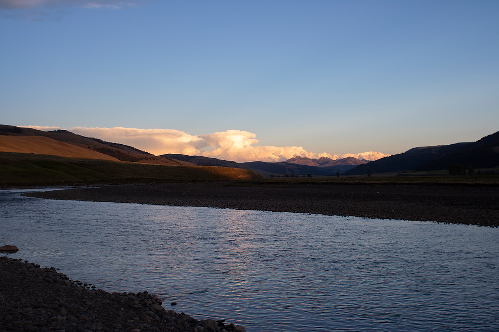 Sunset illuminating the clouds over a mountain ridge looming above a lake in Lamar Valley, Yellowstone National Park