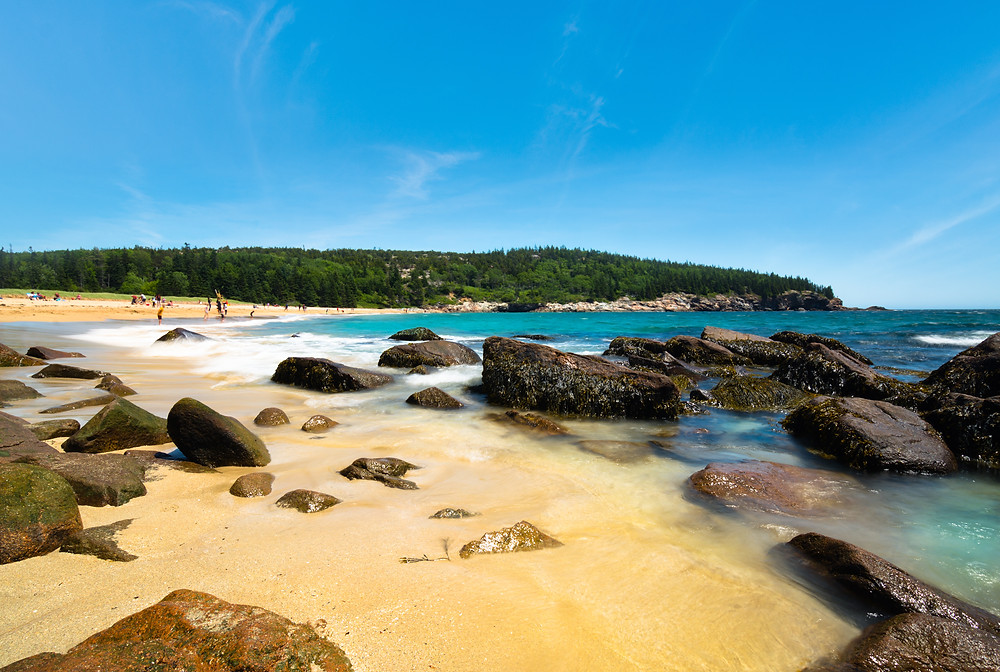 picturesque Sand Beach in Acadia National Park in Maine. Some rocks lie on the bright brown sand, with blue-green waters washing ashore