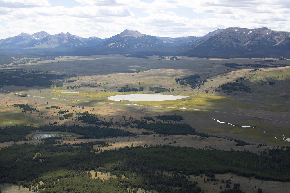A broad, light-speckled view of a lush valley from the top of Bunsen Peak, Yellowstone National Park