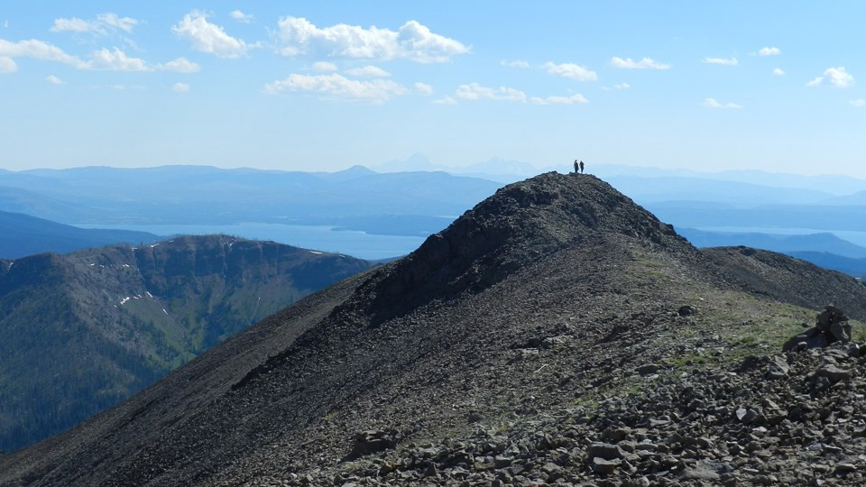 Two people atop the summit of rocky Avalanche Peak in Yellowstone National Park, looking out over an incredible view