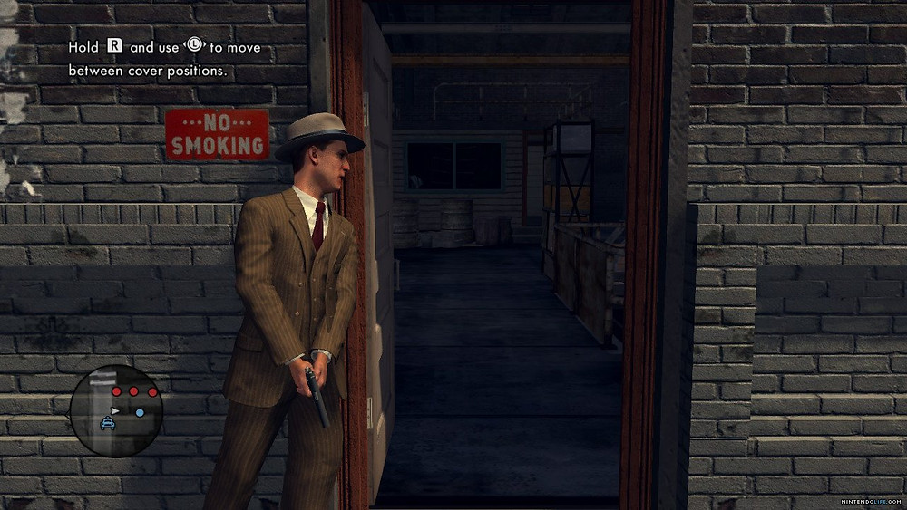 A screenshot of L.A Noire with Cole Phelps taking cover next to an open door with his gun drawn out.