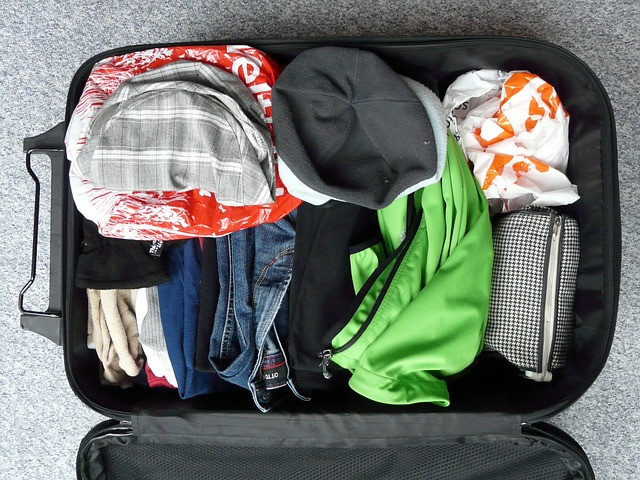 A messy and overstuffed suitcase.