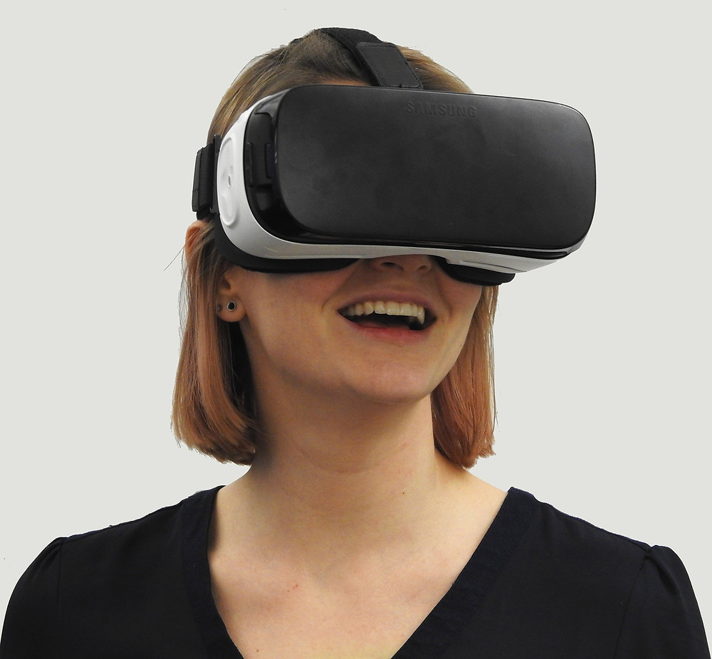 Woman with a VR ehadset smiling behind a white background
