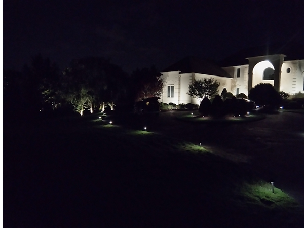 A picture of a home at night with beatiful low voltage landscaping lights illuminating the house and trees