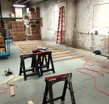 Laying out lumber on ground to start framing walls for storage rooms