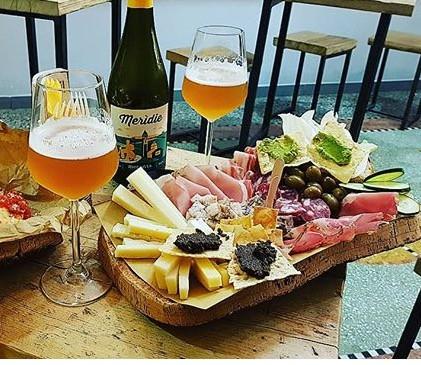 Aperitivo con tabla mixta y cerveza artesana. Fuente: IG @kate_pinna
