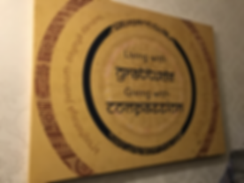 """A poste which says """"living with gratitude, giving with compassion"""" n English and Sanskrit."""