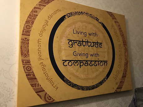 "A poste which says ""living with gratitude, giving with compassion"" n English and Sanskrit."