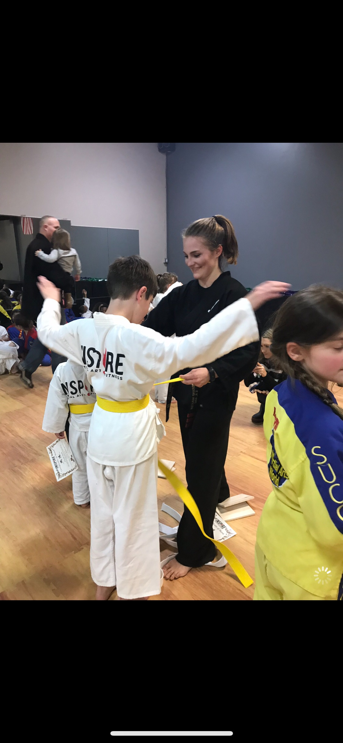Instructor putting on yellow belt on boy
