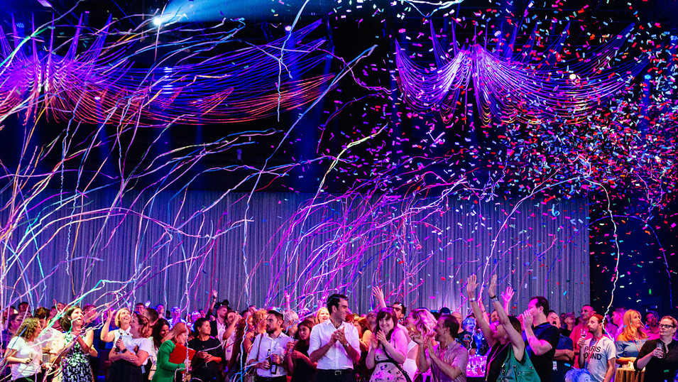 Amazing event photography of people reacting to confetti cannon burst.